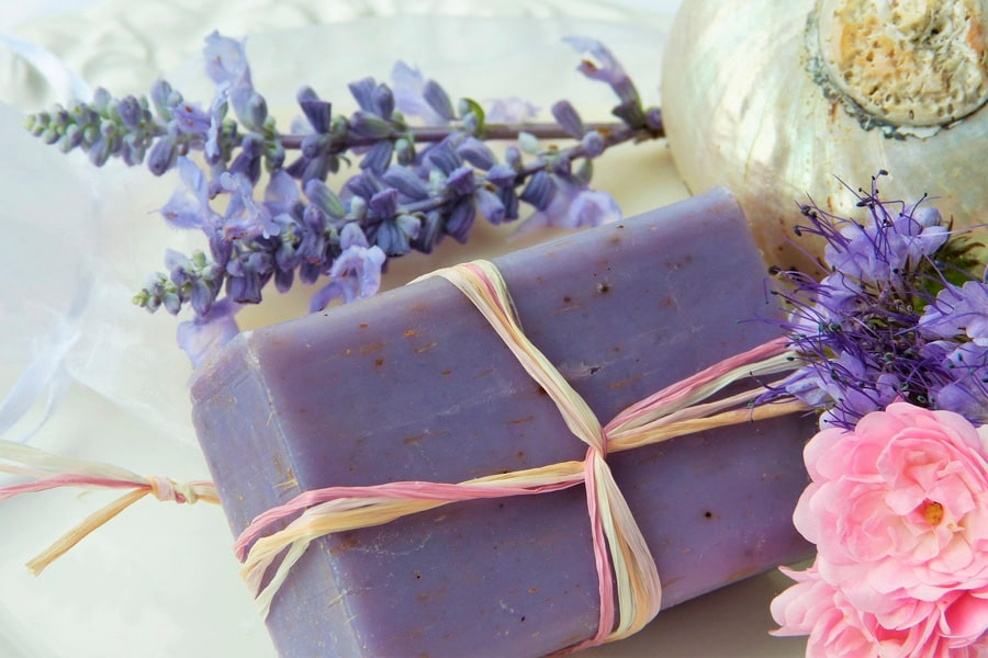 block of homemade lavendar soap and some flowers
