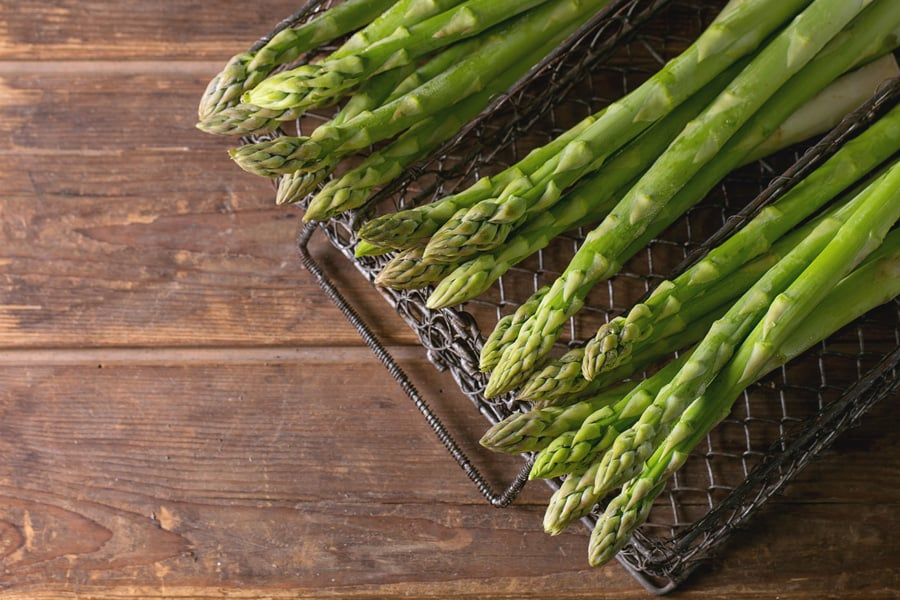 asparagus in a basket on a wooden background