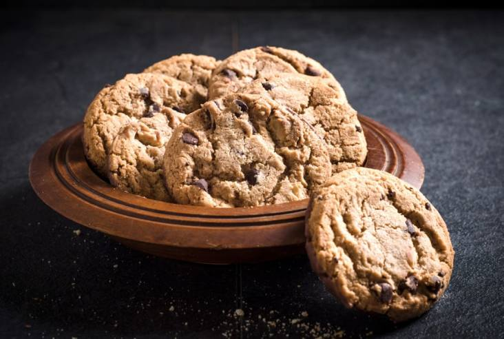 plate of chocolate chip cookies on dark background