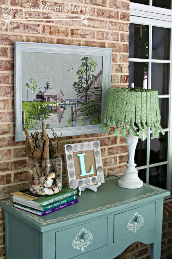 Thrift store needlework art become a showpiece on the screened porch with a new finish to the frame.