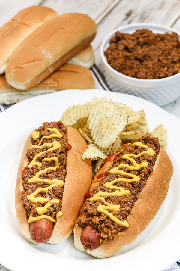 hot dogs with chili with chips on a white plate