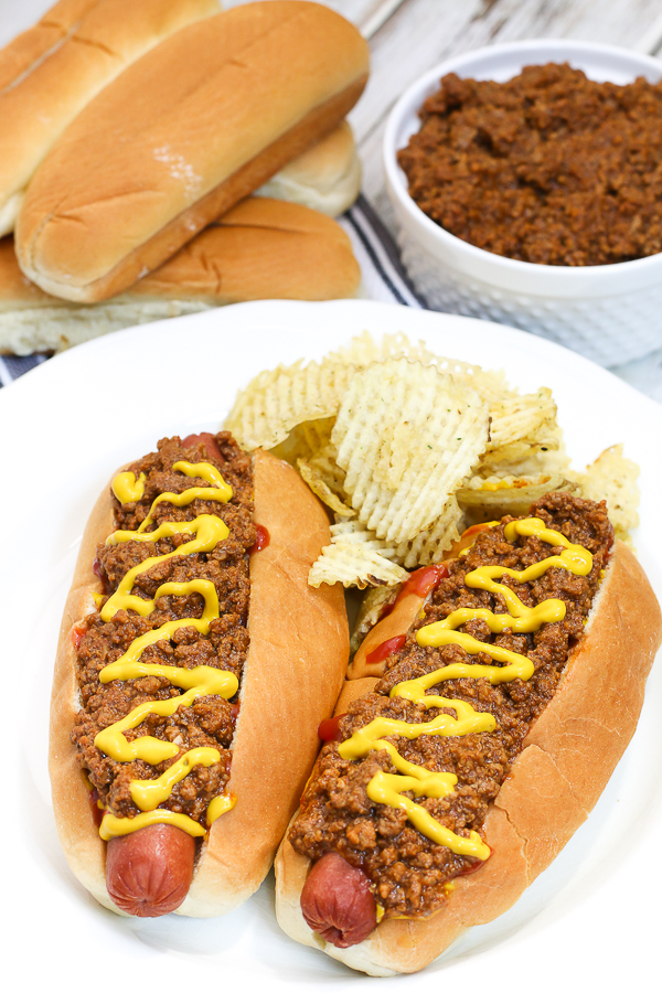 hot dogs with chili and mustard with chips on a white plate