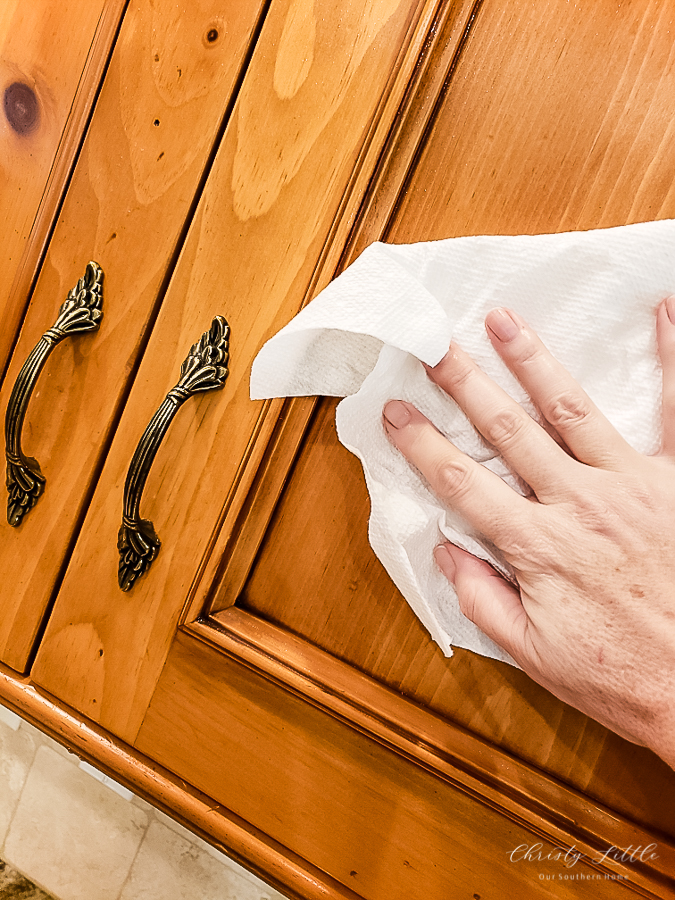 wiping cabinets with towel