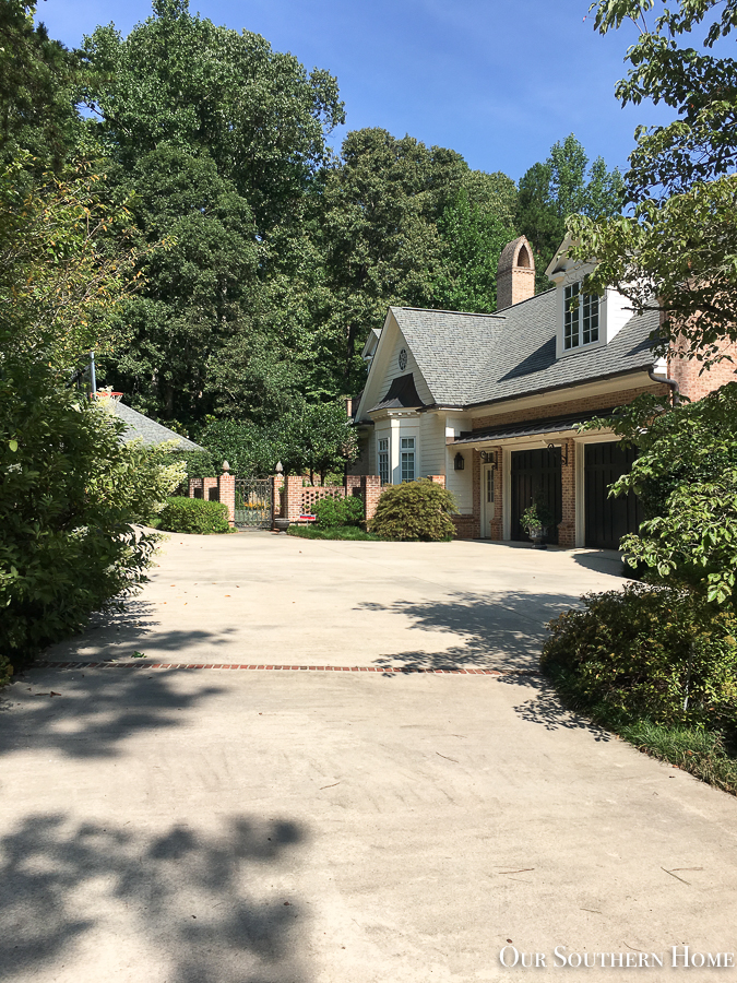 concrete driveway with brick house