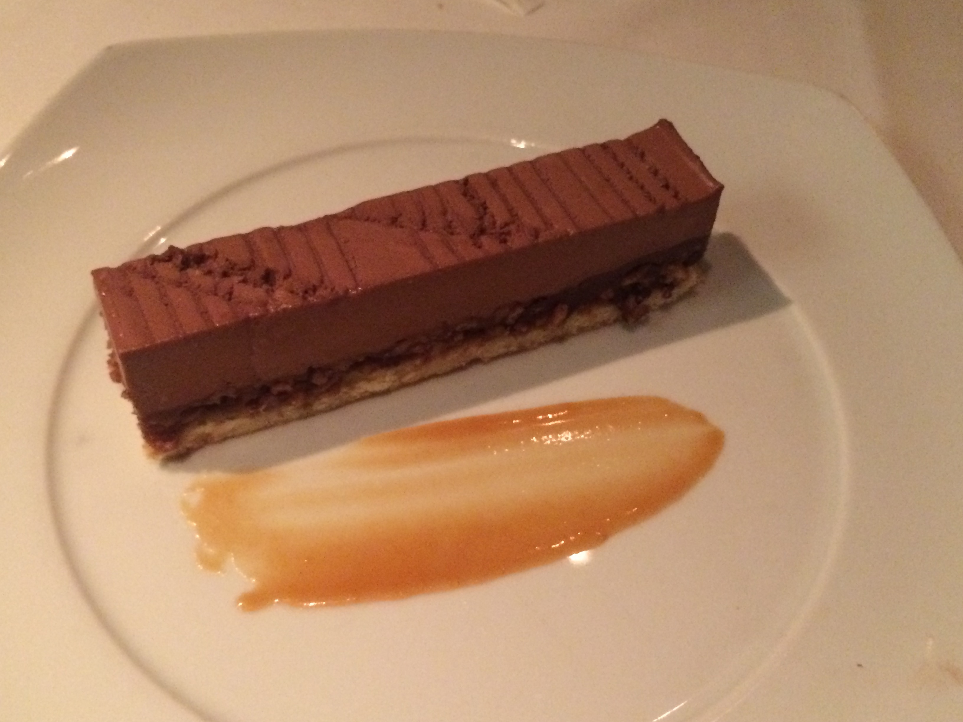 Biscuit Croustillant - a dark ganache crunchy layer of white chocolate and praline topped with chocolate mousse and served with caramel sauce