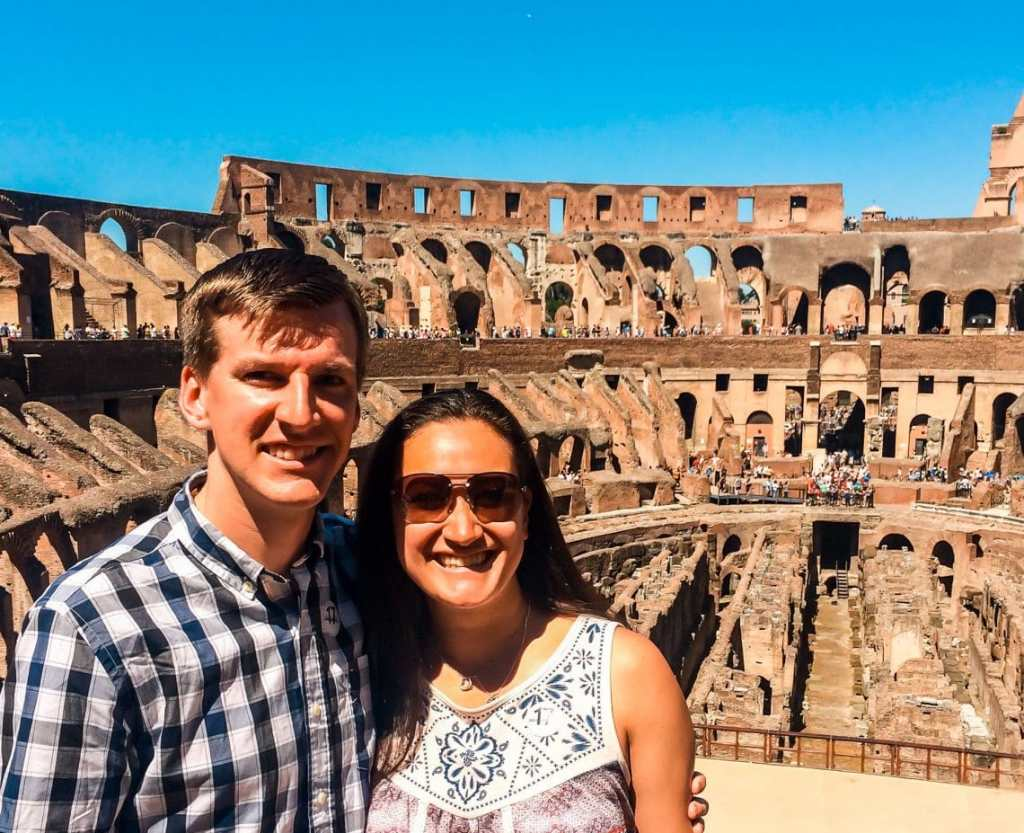 A couple posing and smiling inside the Colosseum during their 2 days in Rome.