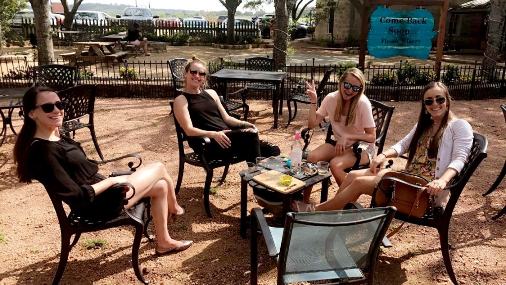 Four women sitting around a table with snacks and wine at Fiesta Winery's outdoor patio.