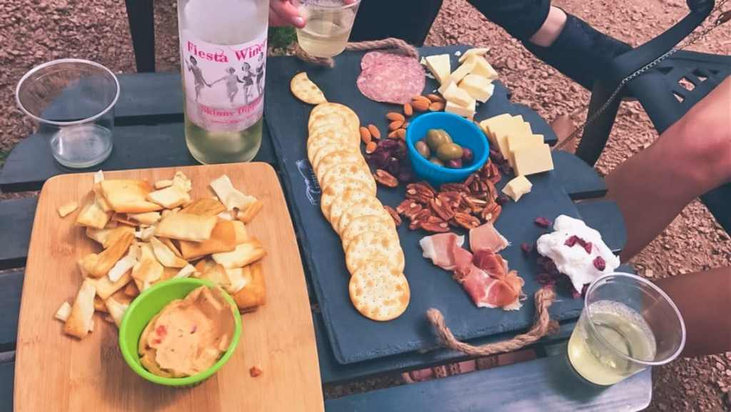 A table full of wine glasses, a board with hummus and pita chips, and a cheese and charcuterie board.