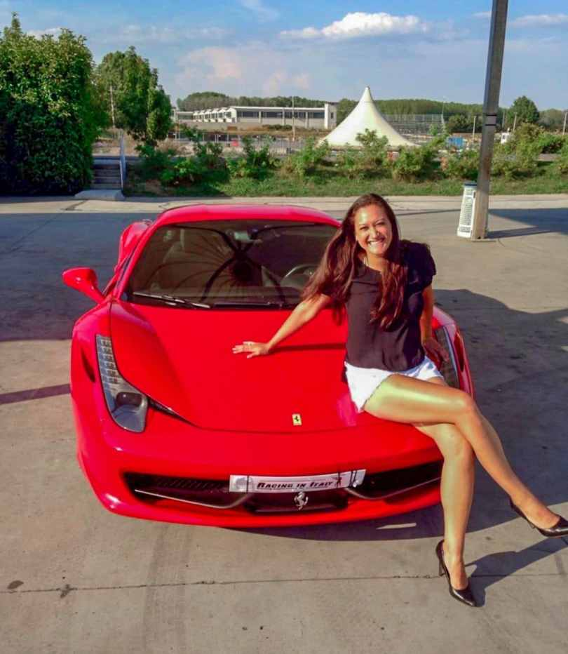 A woman smiling, sitting on top of a red Ferrari 458 with one leg crossed over the other and looking nice in high heels.