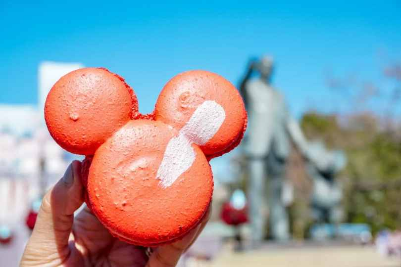 The Raspberry Rose Mickey Macaron is a light red macaron cookie shaped as Mickey Mouse's head filled with a raspberry rose mousse.