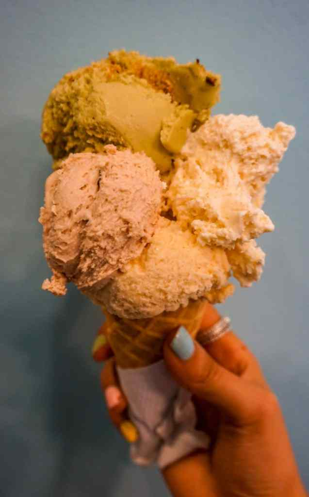 Four giant scoops of gelato (pistachio, amaretto chocolate chip, sea salt caramel, and cheesecake) on a cone from Paciugo.