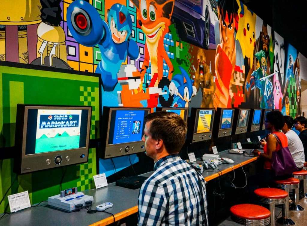 A man playing Nintendo Classic with a row of other gaming consoles and a video game mural on the wall at the National Video Game Museum in Frisco.