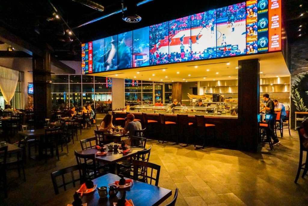 Inside the Sushi Marquee restaurant with TVs above the sushi bar.