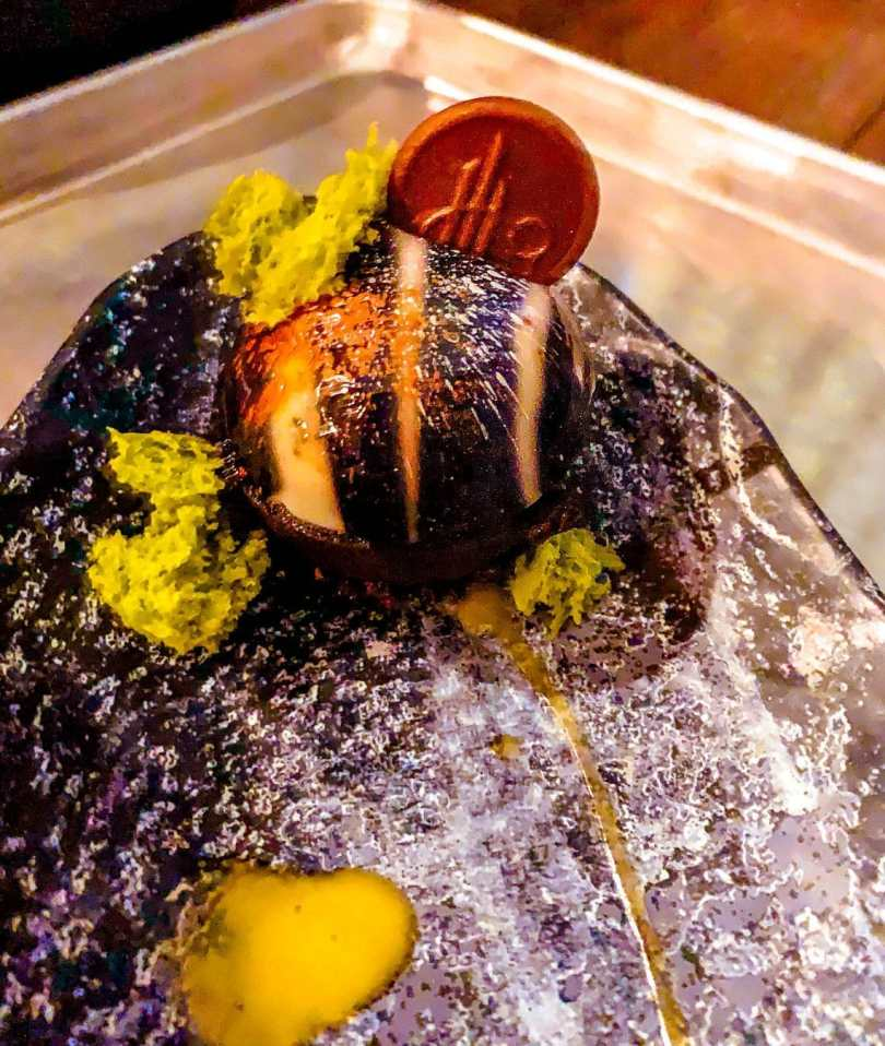 A new dessert in Disneyland called the Batuu-bon which is a chocolate ball with white stripes, and green sponge cake on a plate.