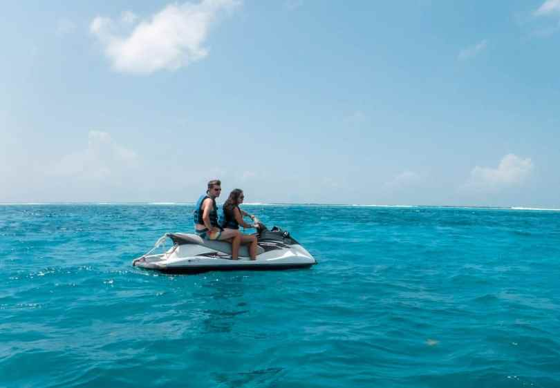 A couple riding on a jet ski in the deep blue ocean because it is one of the best things to do in the Grand Cayman.
