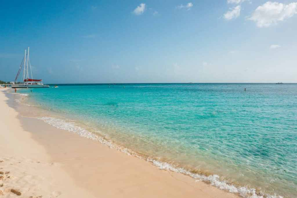 A beautiful photo of a white sand beach and turquoise water in the Grand Cayman.