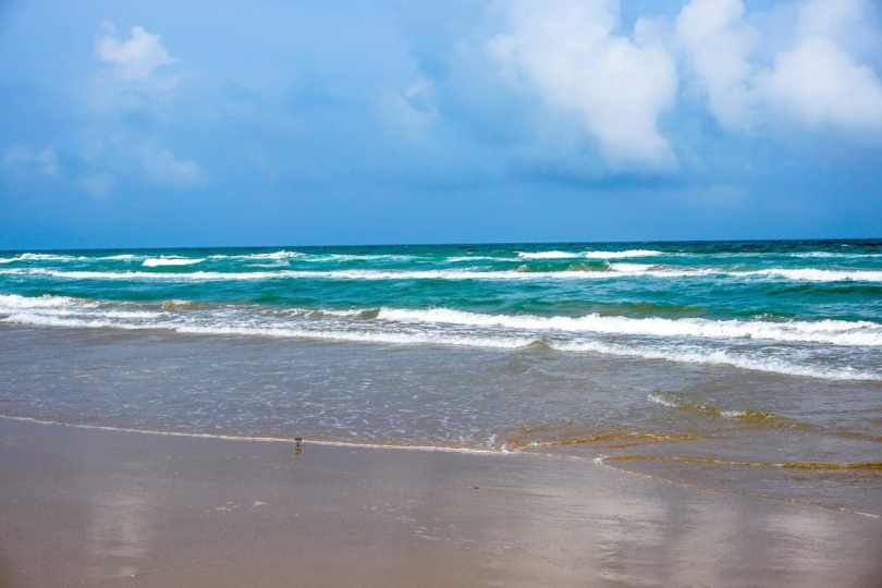 Turquoise blue ocean with small waves coming into shore at the Boca Chica Beach in Brownsville, Texas.