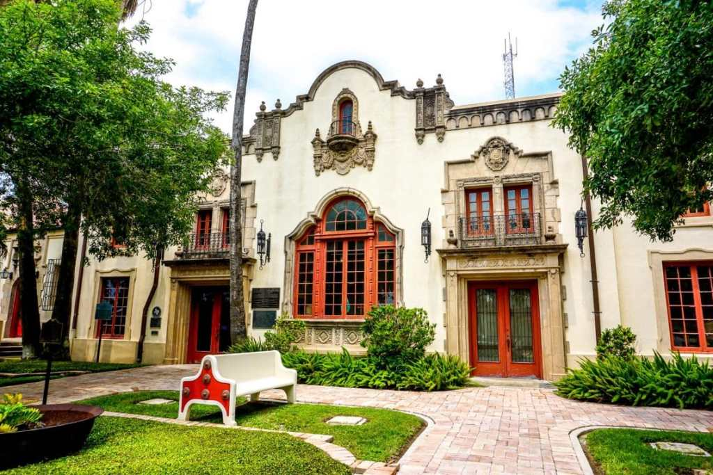 A beautiful historical building in Brownsville, Texas with a red door and window panes.