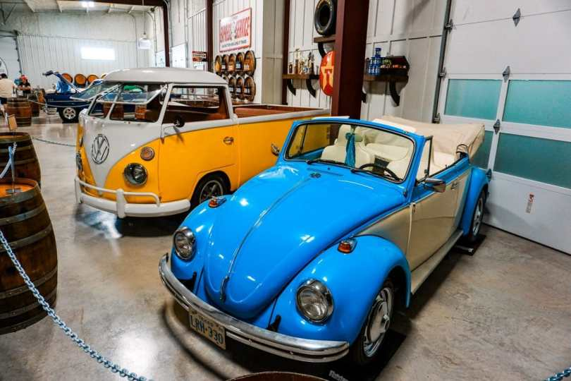 A light blue classic slug bug and a yellow Volkswagen bus behind it.