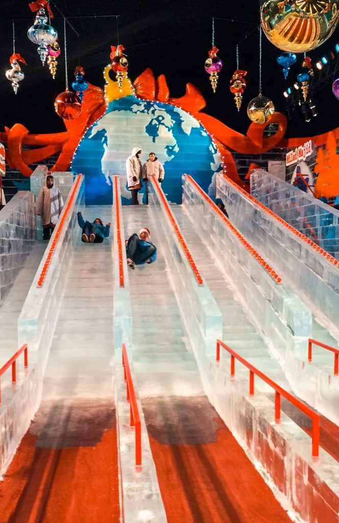 Two people racing down a two-story slide made of ice inside the Gaylords ICE! exhibit.