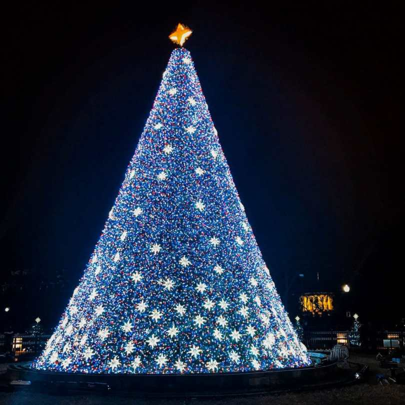 A colorful decorated National Christmas Tree in Washington D.C. with the White House in the background.
