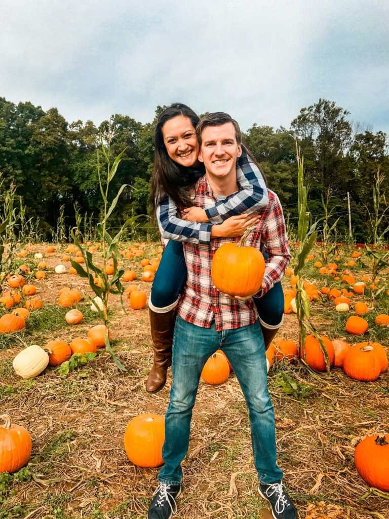 A woman on her husband's back smiling surrounded by a pumpkin patch. This is one of the best things to do in Washington D.C. in the fall.