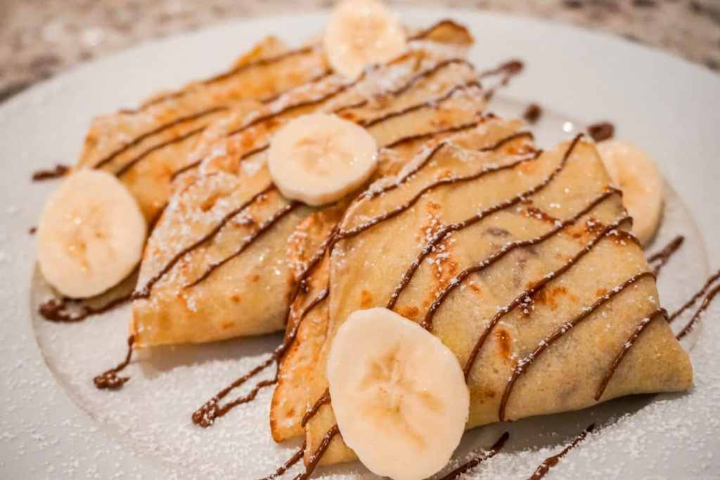 A side photo of three triangular sweet crepes stacked on top of each other filled with fresh bananas and Nutella.