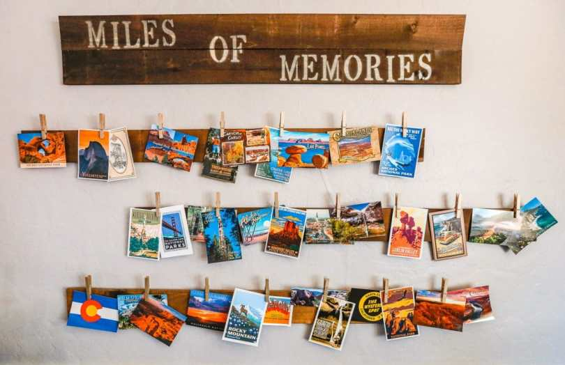 "Several different postcards hanging on the wall with a piece of wood that says ""miles of memories""."