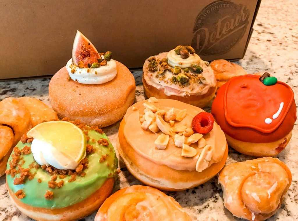 An array of gourmet donuts from Detour Donuts. Pictured is a green Key Lime donut, a red apple donut, a donut with peanuts, and more.
