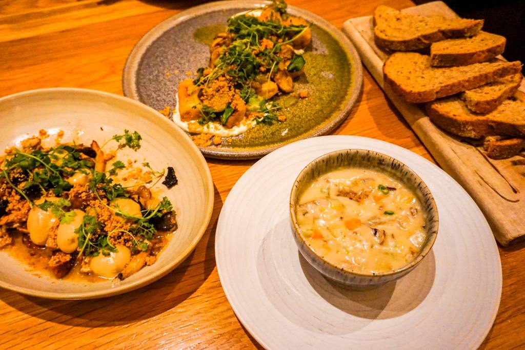 An array of delicious entrees to be shared family style at Forage. A plate full of gnocchi, mushrooms, a bowl of chowder, and sliced bread.