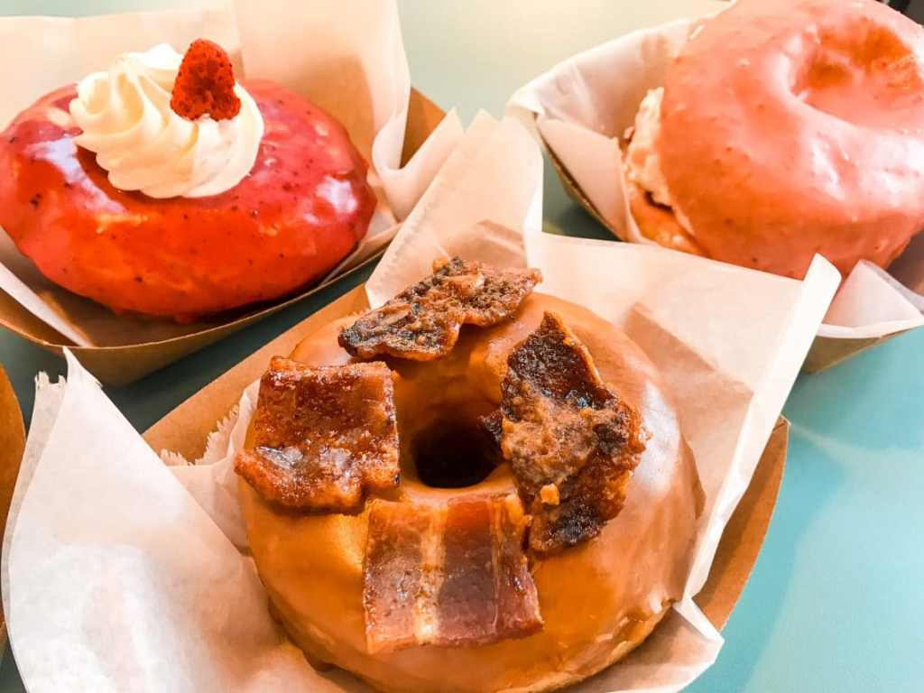 A close up of a maple glazed donut with bacon on top. Two pink donuts are in the background.