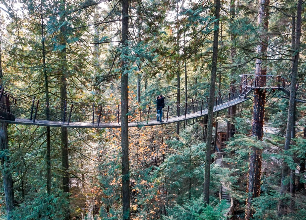 A couple kissing in the middle of a suspension bridge located in Vancouver.