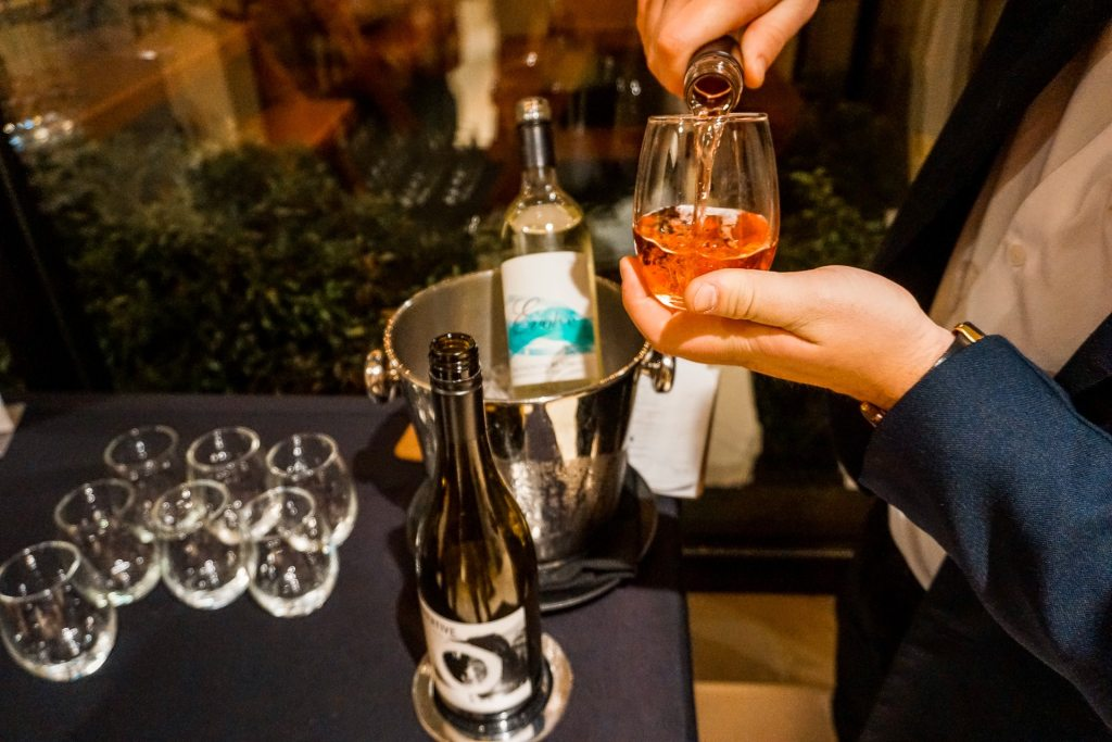 A man pouring a rose wine in a stemless glass for a complimentary wine reception at The Listel Hotel.