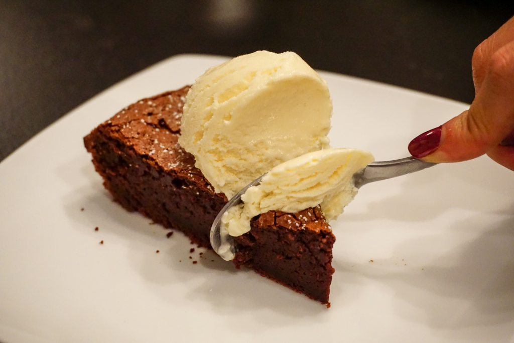 Someone taking a spoonful of Italian flourless chocolate cake known as Torta Tenerina with a scoop of ice cream.