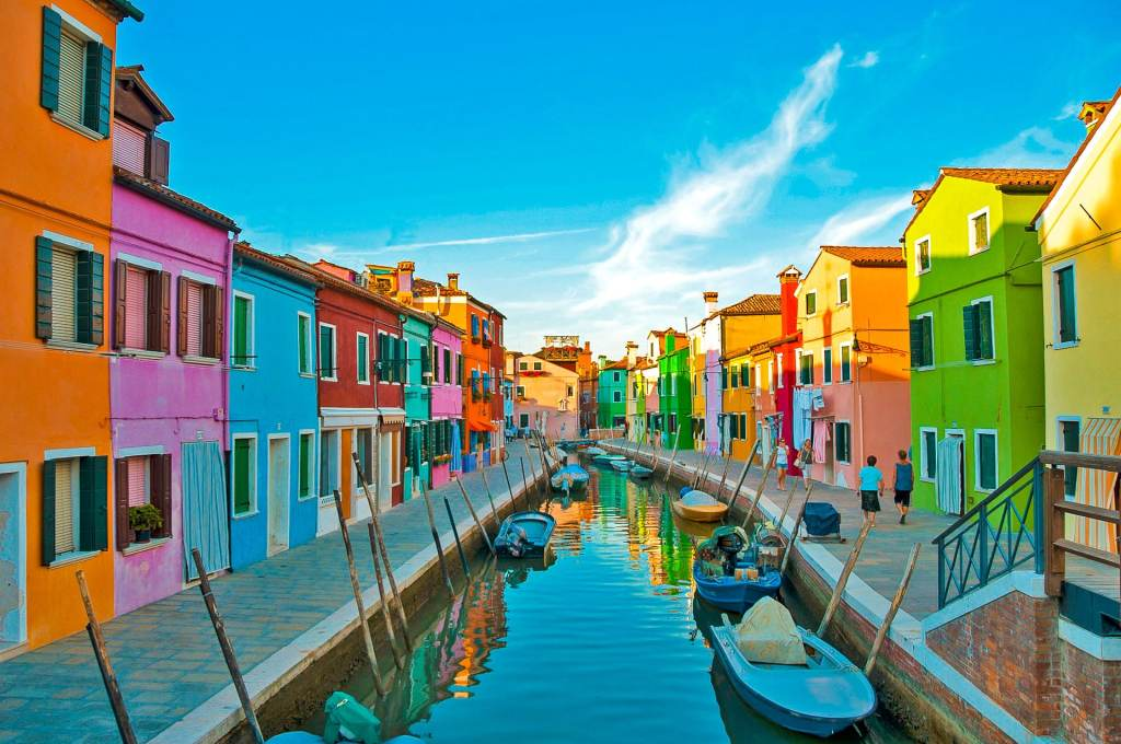 A small canal filled with boats in-between two rows of the most colorful houses in Burano, Italy.