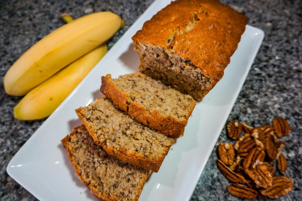 A loaf of the best banana nut bread with three slices on a rectangle plate. On the side are bananas and pecan halves.