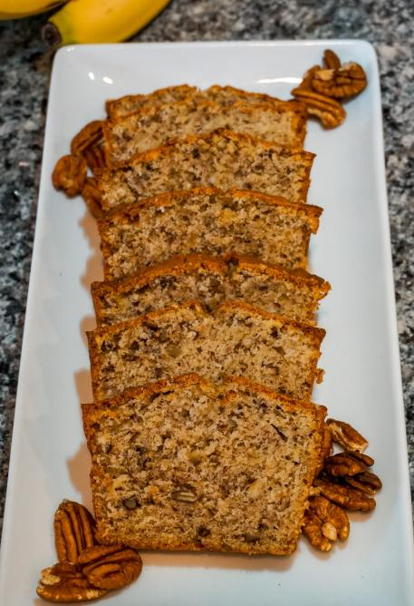 Several slices of banana nut bread in a row on a white rectangle plate with pecan halves.