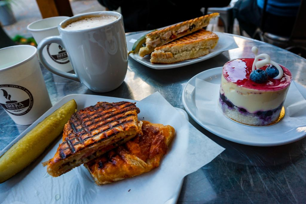 A table with a cup of coffee, plates of Italian sandwiches, and a lemon blueberry cheesecake from Breka Bakery and Cafe in Vancouver - one of the best places to in Vancouver for lunch.