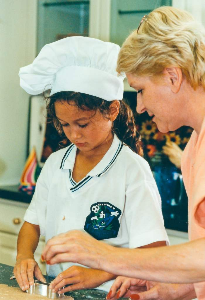 A young girl with a chef hat baking with her grandmother in the kitchen.