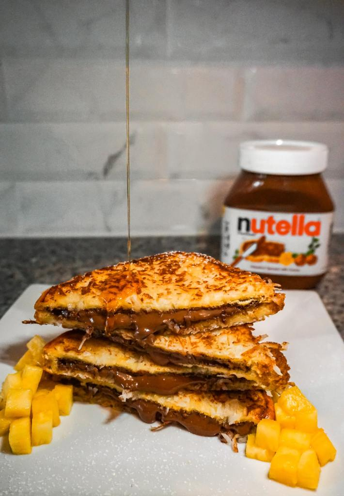 A vertical image of syrup being poured on top of a stack of Nutella filled French toast with coconut.