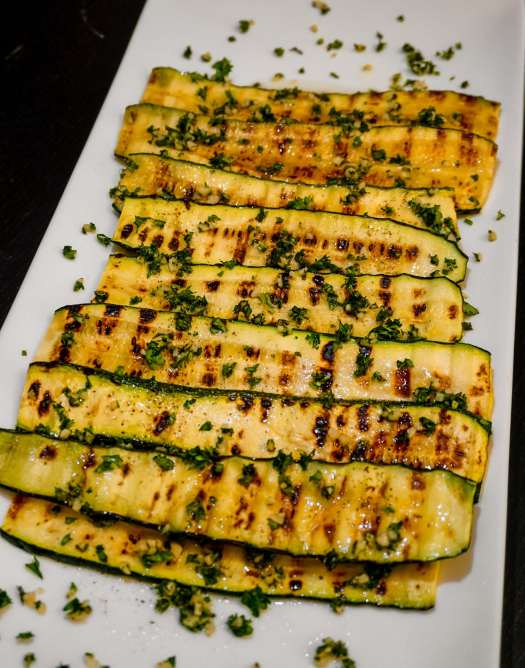 Layers of grilled zucchini with fresh herbs, garlic, and olive oil on a white plate.