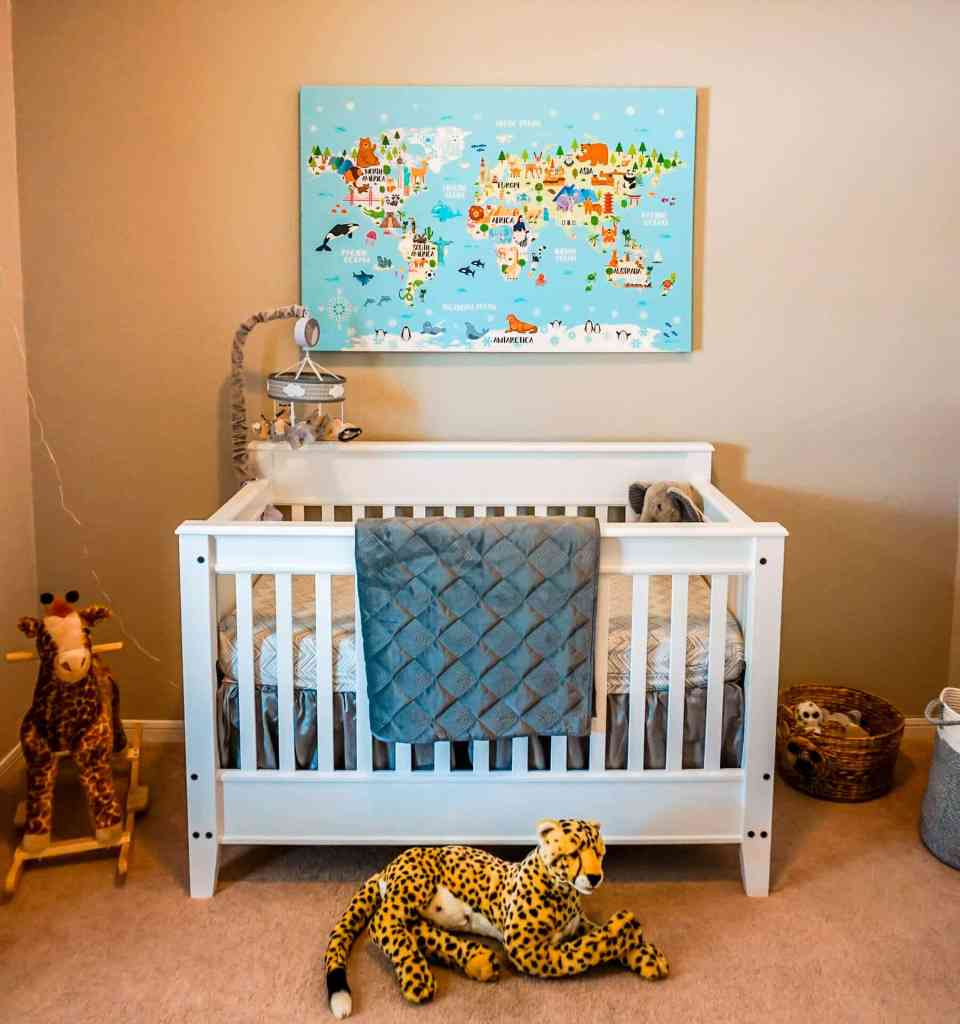 A safari themed nursery with a world map canvas, giraffe rocking chair, cheetah plush toy, white crib with a grey blanket, and more.