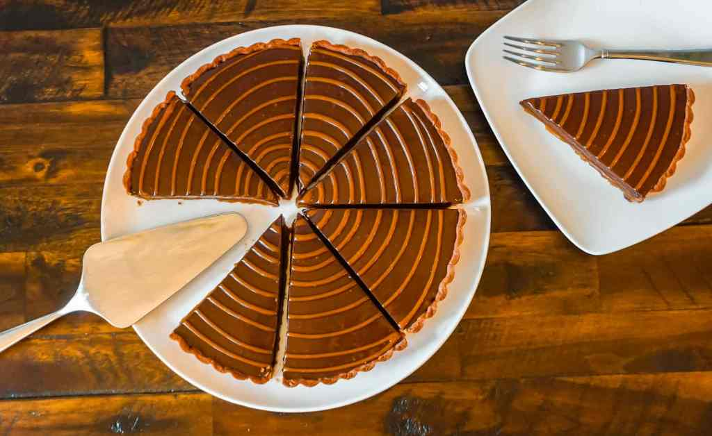 A pie server on a plate with several chocolate caramel tart slices on one plate and a small plate with one slice on the right.