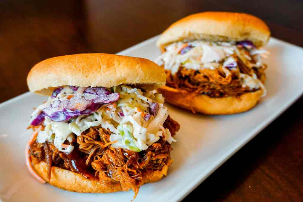 Two Texas pulled pork sandwiches on hamburger buns with coleslaw.