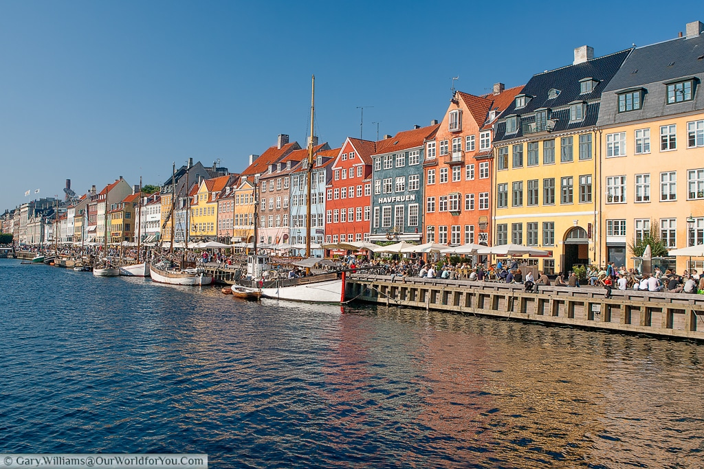 The view of the many bars that line Nyhavn, bathed in beautiful, summer, sunshine, Copenhagen, Denmark