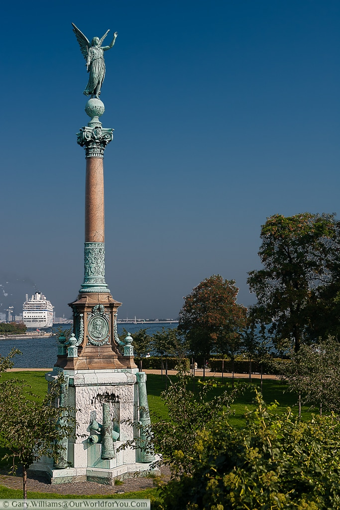 A view of the Ivar Huitfeldt Column in Langelinie, Copenhagen, with a cruise ship moored in the background..