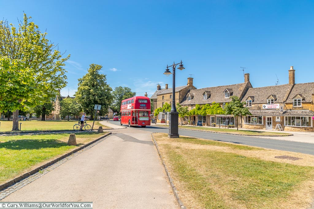 The red bus runs through the village, Broadway, Worcestershire, England, UK