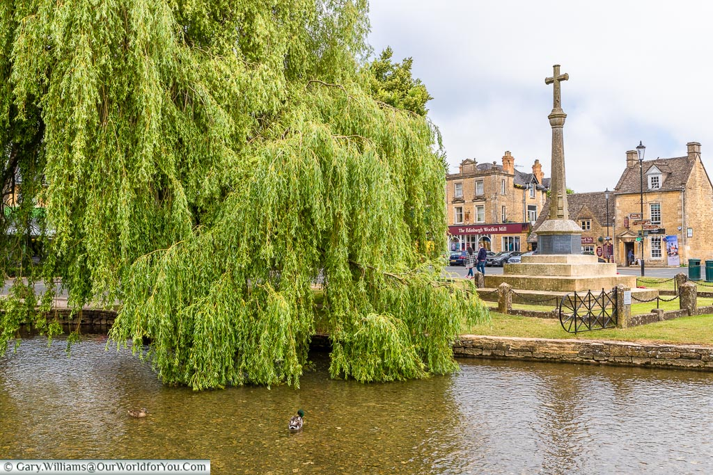 The war memorial across the river, Bourton-on-the-Water, Gloucestershire, England, UK