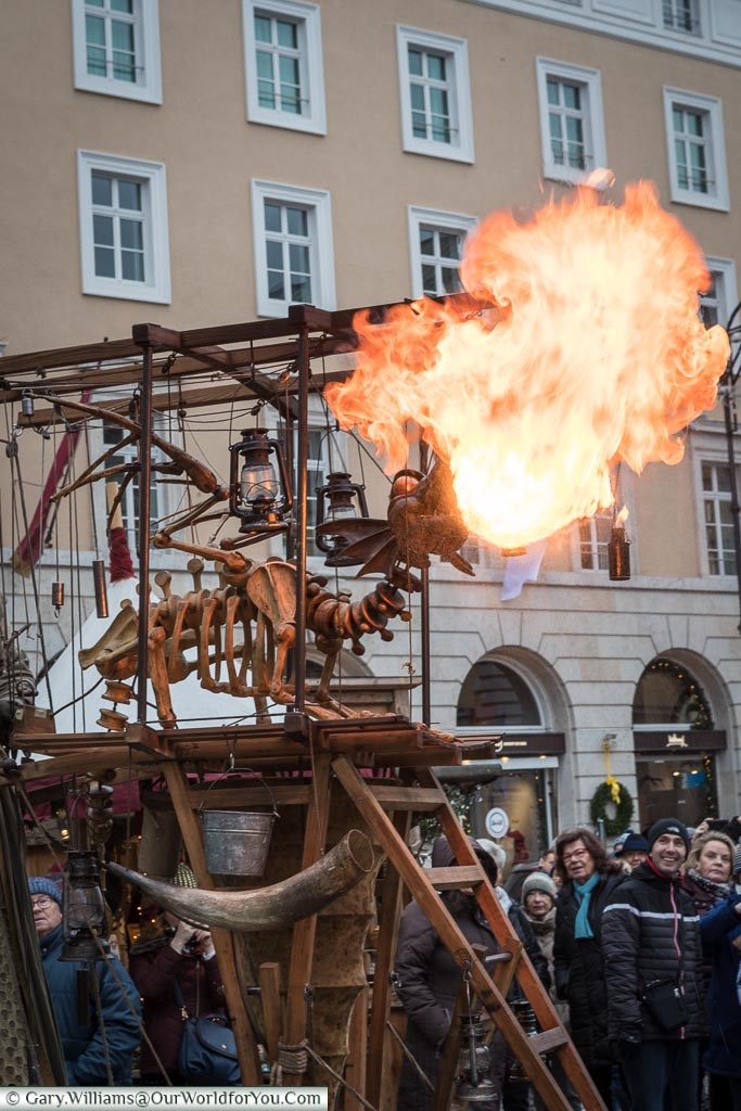 A mobile performance piece of a dragon skeleton puppet breathing flames as the crowds watch on.