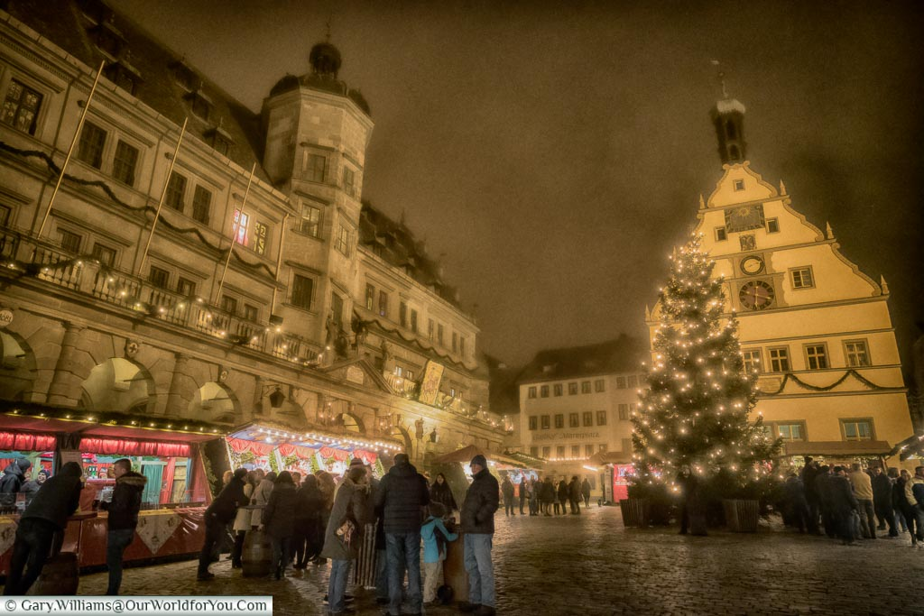 The Marktplatz of Rothenburg ob der Tauber on a misty evening with groups of people huddled together.  There are  a few stalls on the left in front of the Rathaus, and the Christmas tree to the right in front of another historic building.
